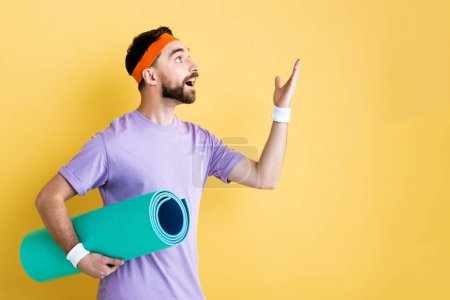 excited sportsman holding fitness mat and pointing with hand isolated on yellow