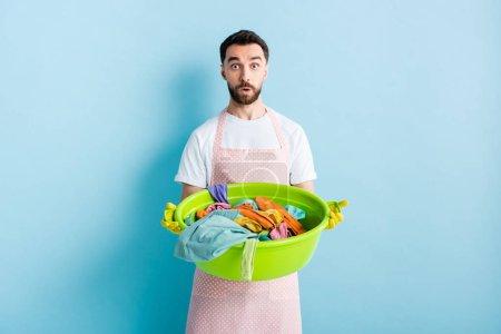 Photo pour Homme barbu choqué tenant bol de lavage en plastique avec buanderie sale sur bleu - image libre de droit