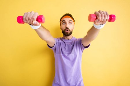 Photo for Selective focus of bearded sportsman exercising with small pink dumbbells on yellow - Royalty Free Image