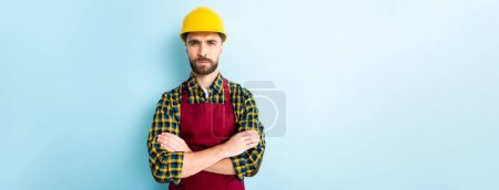 panoramic shot of offended workman in safety helmet standing with crossed arms on blue