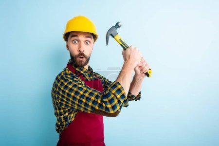 Photo pour Un ouvrier surpris portant un casque de sécurité tenant un marteau bleu - image libre de droit