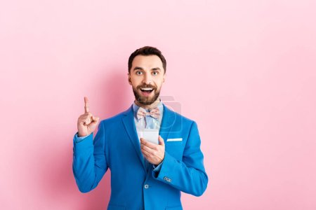 cheerful businessman holding smartphone and pointing with finger on pink