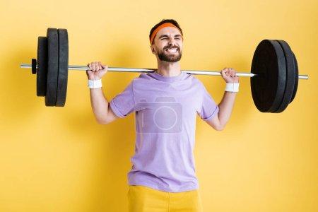 Photo pour Sportif travaillant avec haltère lourde sur jaune - image libre de droit