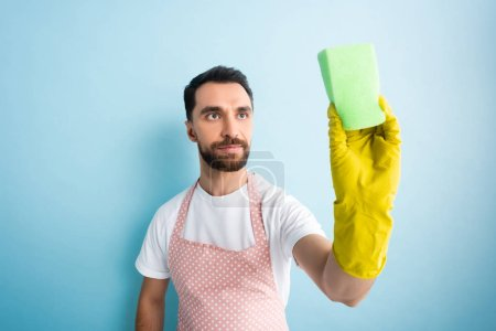 Photo for Selective focus of man looking at sponge on blue - Royalty Free Image