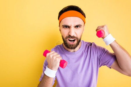 emotional sportsman working out with small dumbbells isolated on yellow