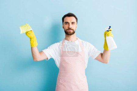 Photo pour Homme barbu tenant un chiffon et un flacon pulvérisateur pour le nettoyage sur bleu - image libre de droit