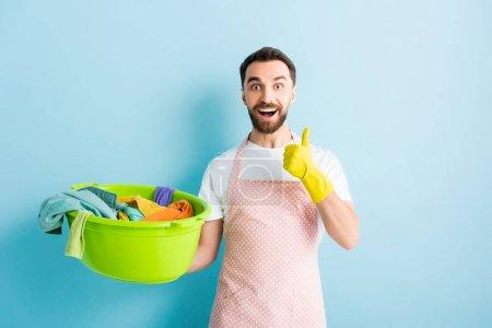 Photo pour Heureux barbu homme tenant bol de lavage en plastique avec buanderie sale et montrant pouce sur bleu - image libre de droit