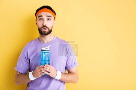 Photo pour Sportif choqué tenant bouteille de sport avec de l'eau sur jaune - image libre de droit