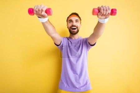 Photo pour Vue à angle bas du sportif excité travaillant avec de petits haltères roses sur jaune - image libre de droit