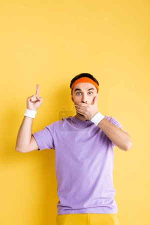 Photo pour Sportif choqué couvrant la bouche et pointant du doigt sur le jaune - image libre de droit