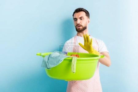 Foto de Impactado hombre celebración de plástico lavabo con ropa sucia y mostrando gesto de parada en azul - Imagen libre de derechos