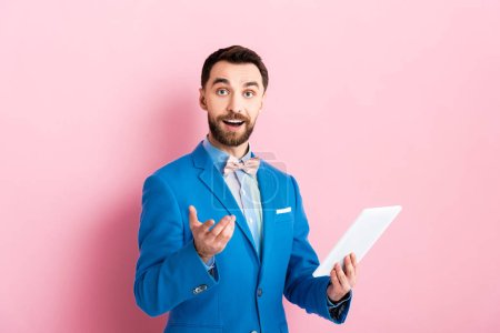 Photo for Cheerful bearded businessman holding digital tablet and gesturing on pink - Royalty Free Image