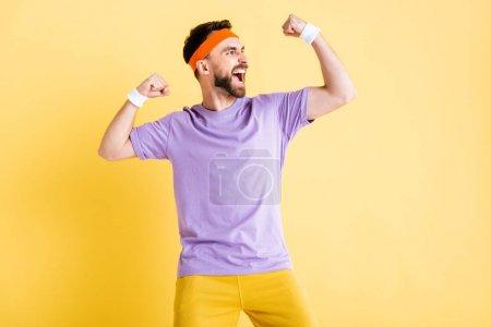aufgeregter bärtiger Mann zeigt Muskeln isoliert auf gelb