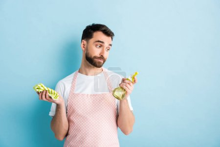Photo for Handsome bearded man looking at rag while holding plastic spray bottle on blue - Royalty Free Image