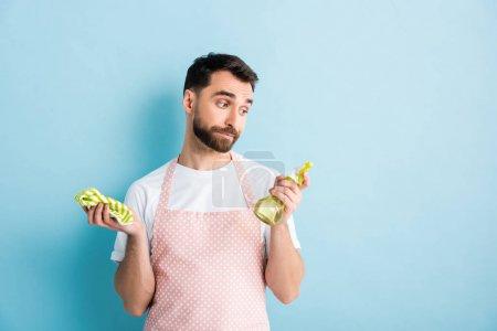 Photo pour Bel homme barbu regardant chiffon tout en tenant bouteille de pulvérisation en plastique sur bleu - image libre de droit