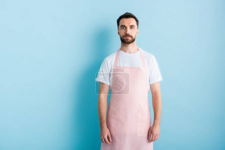 Photo for Handsome bearded man in apron standing on blue - Royalty Free Image