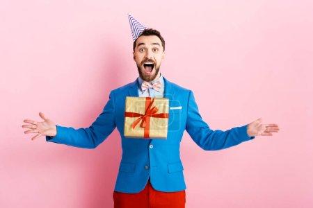 Photo pour Homme d'affaires heureux en coiffe de parti lancer en l'air présent en rose - image libre de droit