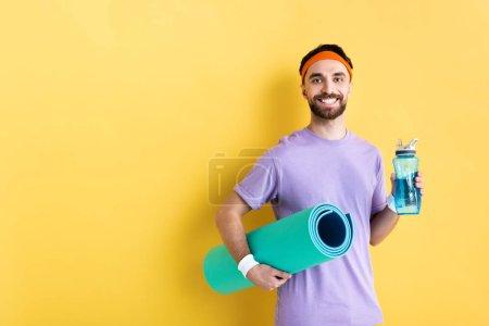 Photo pour Homme barbu positif tenant bouteille de sport et tapis de fitness sur jaune - image libre de droit
