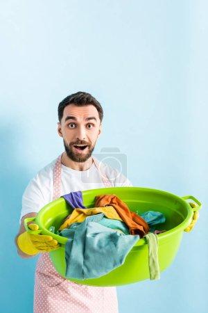 Photo pour Homme choqué tenant bol de lavage en plastique avec buanderie sale sur bleu - image libre de droit