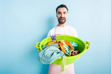 Photo for Cheerful bearded man holding dirty laundry in plastic wash bowl on blue - Royalty Free Image