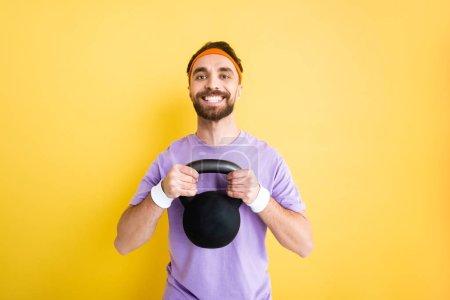 Photo pour Sportif barbu joyeux exercice avec haltère lourd isolé sur jaune - image libre de droit