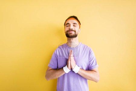 Photo pour Sportif barbu joyeux avec les mains priantes sur jaune - image libre de droit