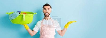 Foto de Foto panorámica del emocionado hombre portador de ropa sucia y apuntar con la mano en azul. - Imagen libre de derechos