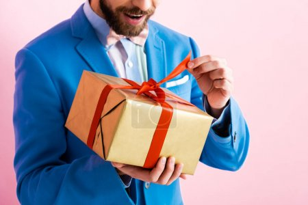 cropped view of excited man in suit touching ribbon on gift box isolated on pink