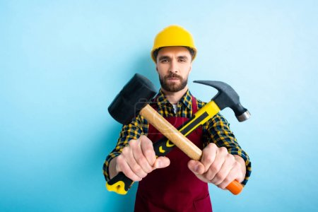 Photo for Selective focus of workman holding hammers on blue - Royalty Free Image