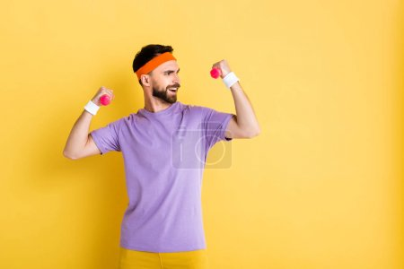 happy bearded sportsman holding small dumbbells while working out on yellow