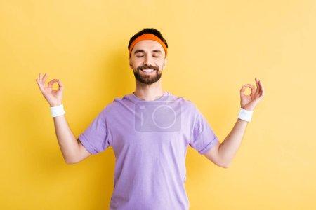 Photo pour Homme gai pratiquant la méditation et souriant sur le jaune - image libre de droit