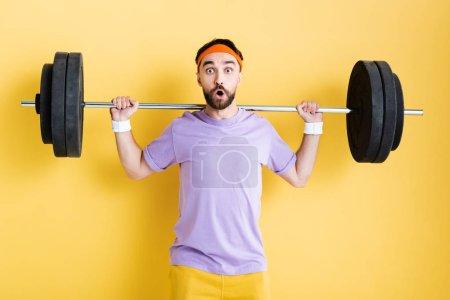 Photo pour Sportif choqué travaillant avec haltère sur jaune - image libre de droit