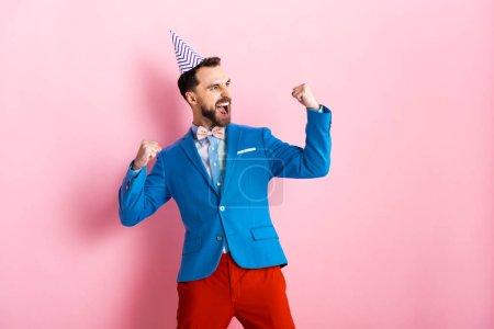 Photo pour Homme d'affaires heureux dans la casquette de fête célébrant sur rose - image libre de droit