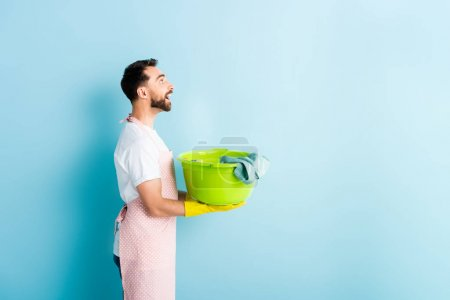 Foto de Vista lateral del feliz hombre portador de ropa sucia en azul - Imagen libre de derechos