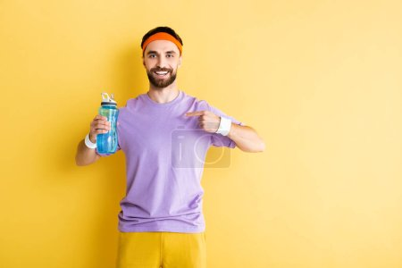 bearded sportsman pointing with finger at sports bottle on yellow