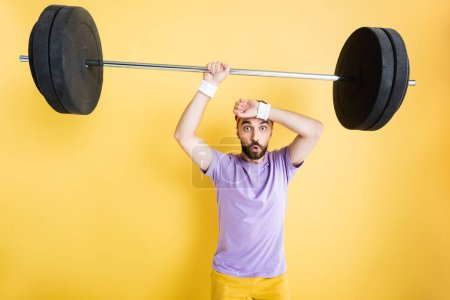 Photo pour Sportif fatigué tenant lourd haltère sur jaune - image libre de droit