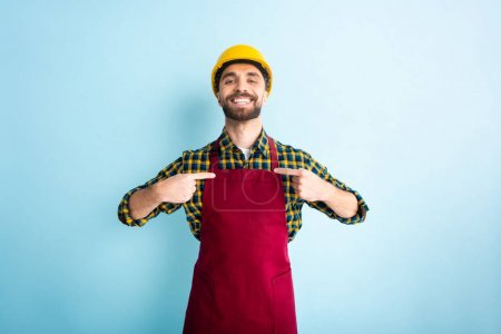 cheerful workman pointing with fingers on blue