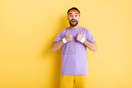 cheerful bearded sportsman showing thumbs up on yellow