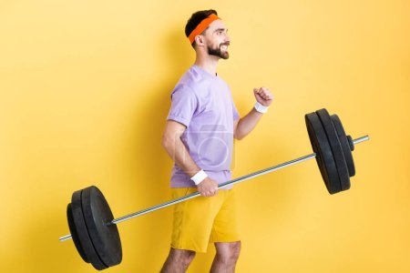 Photo for Side view of happy sportsman holding heavy barbell on yellow - Royalty Free Image