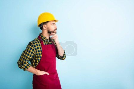 Photo pour Vue latérale de l'ouvrier coûteux debout avec la main dans la poche sur le bleu - image libre de droit