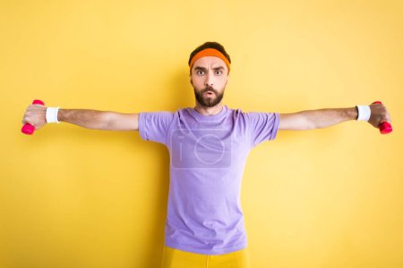 bearded sportsman with outstretched hands holding small dumbbells on yellow