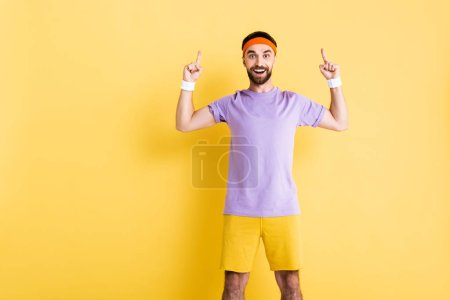 Photo for Happy man in headband pointing with fingers on yellow - Royalty Free Image