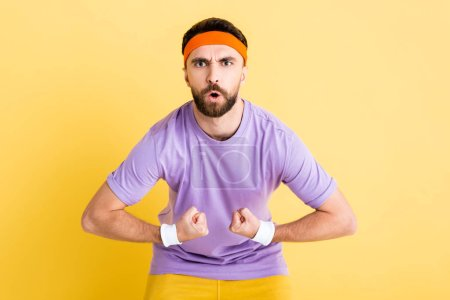 Photo for Bearded sportsman in headband showing muscles isolated on yellow - Royalty Free Image