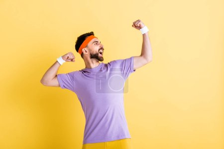 Photo for Happy winner in headband screaming while celebrating on yellow - Royalty Free Image