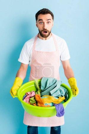 Photo pour Homme choqué dans des gants en caoutchouc tenant bol de lavage avec buanderie sale sur bleu - image libre de droit