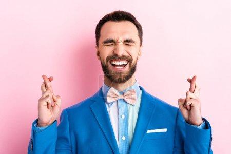 Photo pour Homme barbu en costume avec les doigts croisés sur rose - image libre de droit