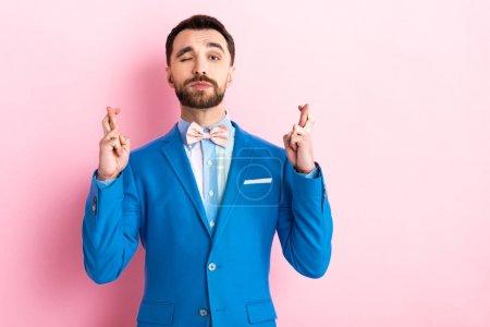 Photo pour Homme barbu en costume avec doigts croisés clignotant les yeux sur le rose - image libre de droit