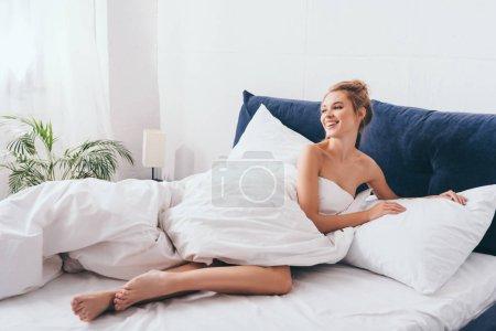 Photo pour Belle femme souriante couchée en draps sur le lit le matin - image libre de droit