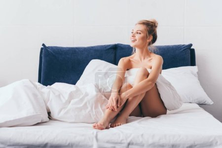 Photo pour Attractive happy woman in sheets sitting on bed in morning - image libre de droit