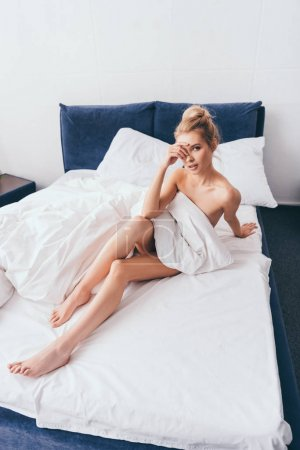 Photo pour Attractive blonde woman sitting in bed with sheets in morning - image libre de droit